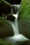 Waterfall and Mossy Rocks. Small mountain stream waterfall through moss covered rocks Royalty Free Stock Photo