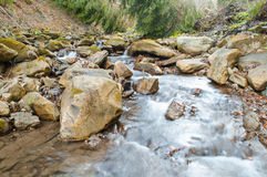 A waterfall on a mountain river Stock Photos