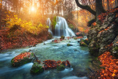 Waterfall at mountain river in autumn forest at sunset. Royalty Free Stock Photography