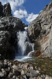 Waterfall on mountain river and blue sky with clouds Stock Photography