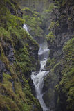Waterfall on the mountain river in the rocky rift. Norway Stock Photography