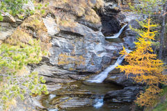 Waterfall in the mountains and the autumnal trees, long exposure Stock Images
