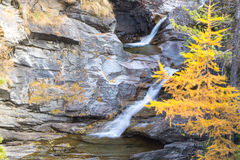 Waterfall in the mountains and the autumnal trees, long exposure Stock Photo