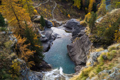 Waterfall in the mountains and the autumnal trees, long exposure Royalty Free Stock Photo