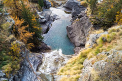 Waterfall in the mountains and the autumnal trees, long exposure Royalty Free Stock Images
