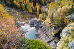 Waterfall in the mountains and the autumnal trees, long exposure Royalty Free Stock Image