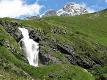 Waterfall and mountains near Engelberg, Switzerland. Waterfall and mountain peaks seen from a valley near Engelberg, Switzerland royalty free stock images