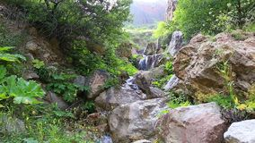 Waterfall in the mountains near the village stock footage