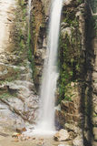 Waterfall in the mountains. Water falls from the mountain down to the rocks. It is photographed on an excerpt. royalty free stock photography