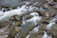 Waterfall in the mountains. Water runs throught the stones Royalty Free Stock Images