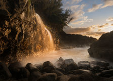 Waterfall near Queens Bath in Princeville Kauai. Setting sun at sunset illuminates a small waterfall falling into the ocean as a local fisherman waits for a bite Stock Photo