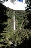 Waterfall in New Zealand. Waterfall named Humboldt Falls in Hollyford Valley, Fiordland National Park, New Zealand on a sunny day Stock Images