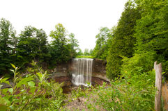 Waterfall off rocky cliff in forest royalty free stock photography