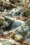 Waterfall over icy rocks. Closeup of waterfall flowing over icy rocks with slow motion blur Stock Images