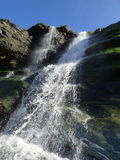 Waterfall over mossy rocks. Spacing over the rocks light shinning though Stock Images
