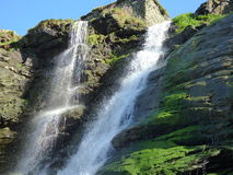 Waterfall over mossy rocks. Spacing over the rocks light shinning though Royalty Free Stock Photography
