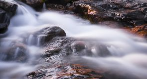Waterfall over red rock. Three steps waterfall in long-time exposure Royalty Free Stock Photos