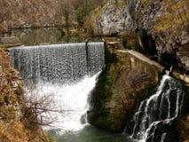 A waterfall over a river dam Stock Photos