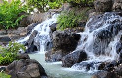 Waterfall over the rocks. This waterfall pours over some large rocks in Hawaii Royalty Free Stock Photos