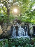 Waterfall in a park. Waterfall over rocks in a park with sun shining through the trees on a hill Royalty Free Stock Photography