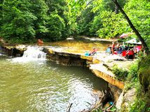 Waterfall. People enjoying summer day playing swimming water creek getaway hidden oaise rocky ledge pouring nature outdoors Royalty Free Stock Images