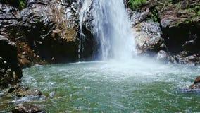Waterfall from Pond Rocks to Foamy Stream Top among Green Rocks stock video