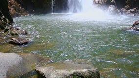 Waterfall from Pond Rocks to Foamy Stream Top among Green Rocks stock video footage