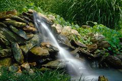 Waterfall pouring down rocks Royalty Free Stock Photo