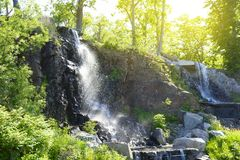 Waterfall in a public place on the Russian island under the rays of a bright sun Stock Photography