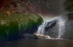 Waterfall with rainbow. Waterfall in line(slow shutter speed) with art work rainbow Stock Photo