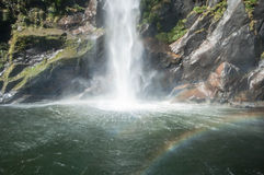 Waterfall and rainbow. Milford Sound. Stock Photo