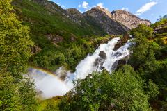 Rainbow and Briksdal waterfall in Norway. Waterfall and rainbow on the way to Briksdal or Briksdalsbreen glacier in Olden, Norway and green mountains royalty free stock image
