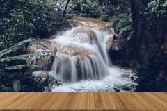 Waterfall in rainforest. cascade in forest. water flowing in tro. Pical jungle in spring with wood table for display product Stock Image