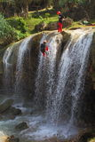 Waterfall Rapelling Sport. Adrenaline rising sport where people are climbing down waterfall to reach the bottom Stock Image