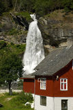 Waterfall and red house in norway - scandinavia Stock Images
