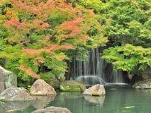 Waterfall and red leaves in autumn season at Koko-en garden, Himeji, Japan. Royalty Free Stock Images