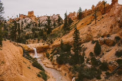 Waterfall among red rocks and trees Royalty Free Stock Image