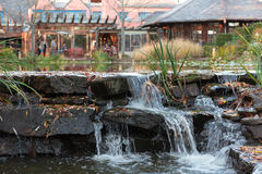 Waterfall by Restaurant. Man-made waterfall by a restaurant with indoor and outdoor seating Stock Photography