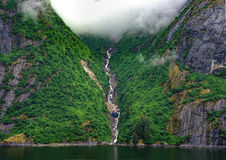 The Waterfall. A ribbon waterfall cascading down the cliffs of the Tongass National Forest into Tracy's Arm fjord in Alaska Stock Photo