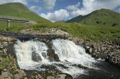 Waterfall on River Cluanie. With Cluanie Lodge Bridge Royalty Free Stock Photo