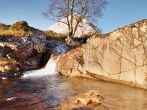 Waterfall on river Coupall at delta to river Etive. Snowy mountain Stob Dearg 1021 metres high Royalty Free Stock Photography