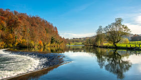 Waterfall on the river. Dam on the river blue sky reflection of trees in water Stock Image