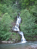 Waterfall. And river in mountains among green trees Stock Photos