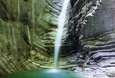 Waterfall in a rock with shiny water lit by sunlight water Stock Photography