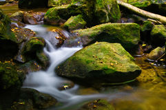 Waterfall and rocks. Closeup of small waterfall in slow motion blur with moss covered rocks Royalty Free Stock Photography