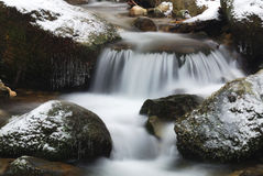 Waterfall on the rocks. Ice on the rocks into the stream Stock Image
