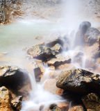 Waterfall and rocks. In mountain Stock Images