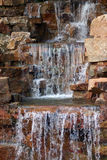 Waterfall and Rocks. Water falling over red rocks and forming a pool Royalty Free Stock Photos