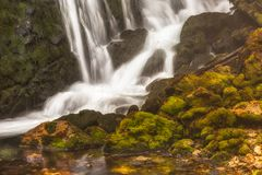Waterfall among rocks covered Stock Image