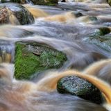 Waterfall with rocks in forest. Waterfall with black and green rocks in forest stock photography